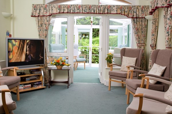 Bright lounge area, with a TV and conservatory