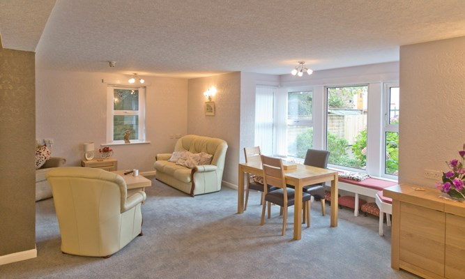 A bright cosy lounge area with seating areas for residents
