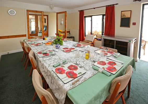 Communal dining room with set table where residents share meals together
