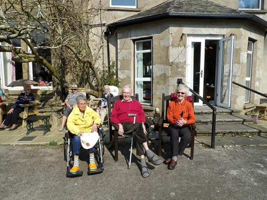 Residents are sat outside the house in the sun
