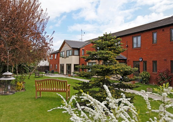 Beautiful garden at Abbeyfield House with bench and tables where residents can enjoy the sunshine
