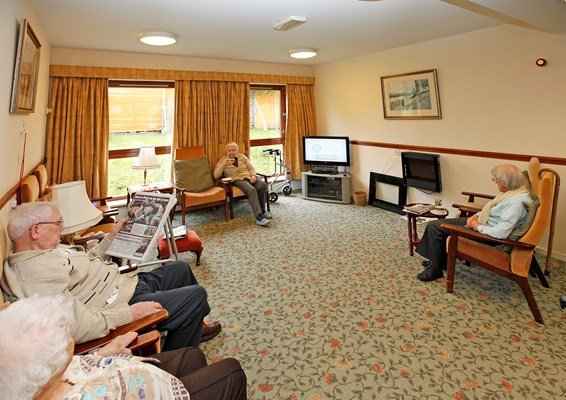 Residents are sat in the lounge reading and watching tv