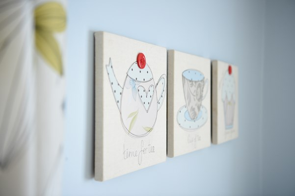 Three canvas pictures on a wall showing teapots and cups
