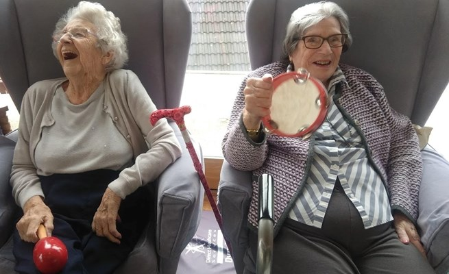Two residents enjoying a musical activity