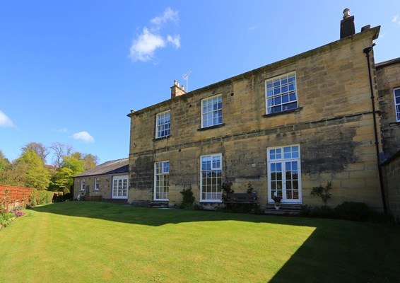 The back of the house and bright well kept lawn
