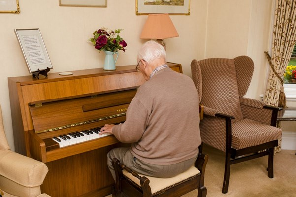 A resident is sat playing the piano