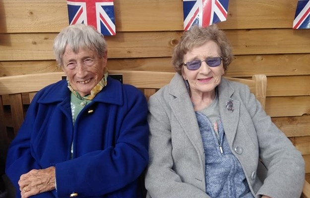Two residents smiling under union jack bunting