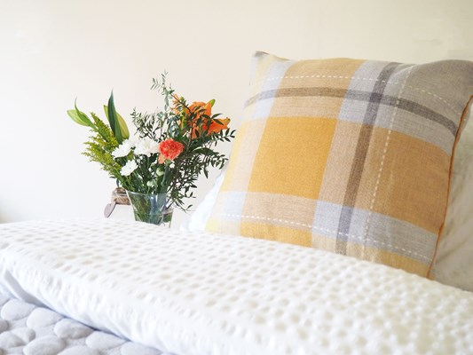 A yellow cushion on a bed with vase on the bedside