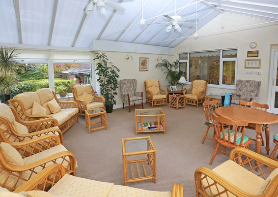 A large conservatory with chairs and sofas and a table in the corner