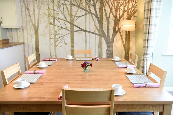 Close up of a set dining table with tree wallpaper in the background