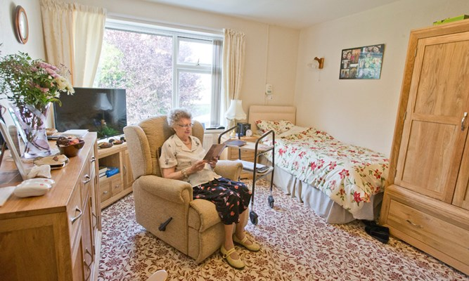 A resident is sat reading in her bedroom