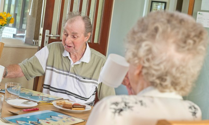 Residents are sat at the table enjoying tea and biscuits