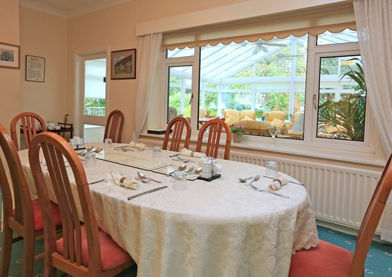 A large dining table set for dinner with a view of the conservatory through the window
