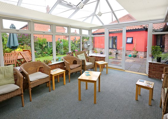 Bright conservatory overlooking the garden with plenty of seating for residents