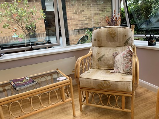 Armchair next to the window in the conservatory for residents to enjoy at Abbeyfield House, Banbury