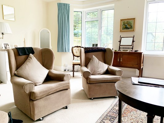 Bright room with large windows with cosy armchairs