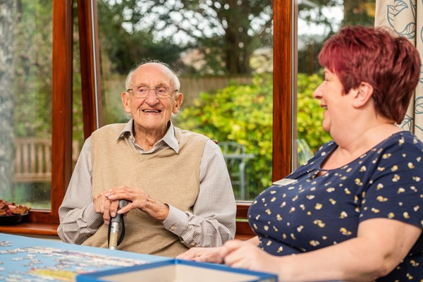 Resident and member of staff laugh together at Culver House