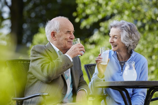 A man and a woman enjoy refreshments in the garden