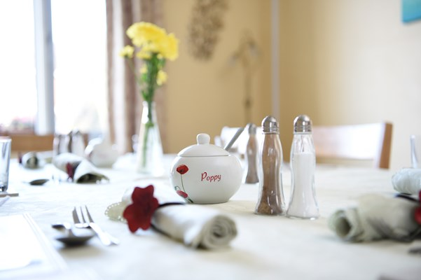 A close up of the dining table with napkins and cutlery