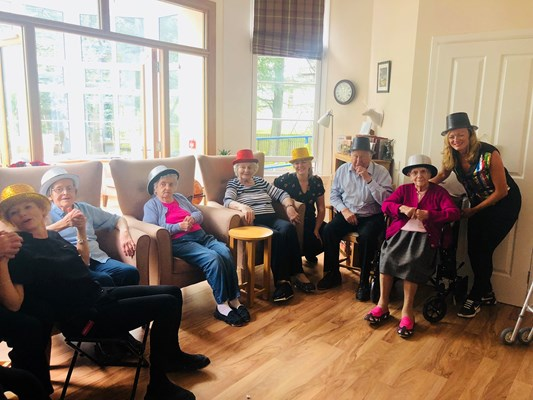 A group of residents sat together wearing party hats