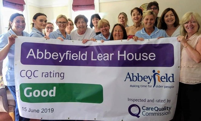Staff members stood being their CQC rating banner saying good