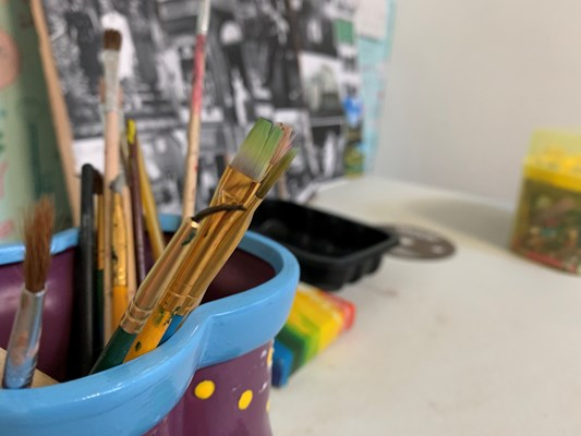 Paint brushes rest within a paint pot