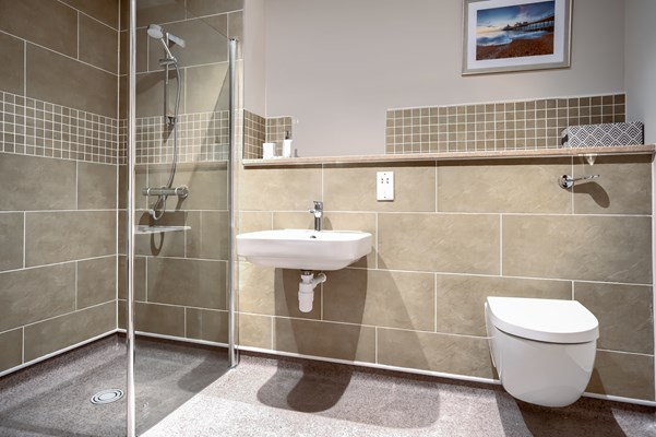 A fully tiled bathroom with walk in shower and modern features