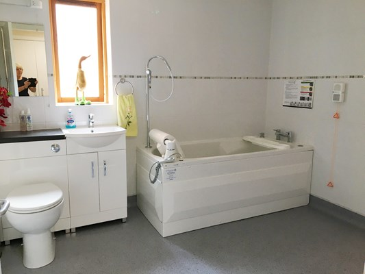 Bathroom with tub, sink, cabinets and toilet at Rider House