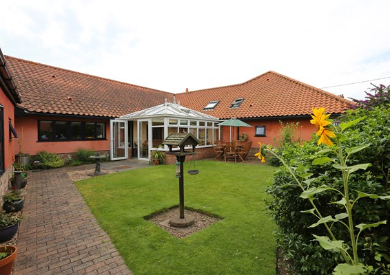 Beautiful garden with a bird feeder, plant pots, conservatory and seating area for residents to enjoy