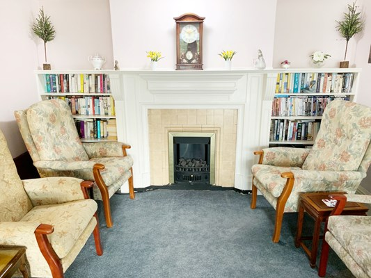 Armchairs next to fireplace and bookcases filled with books at The Wyke