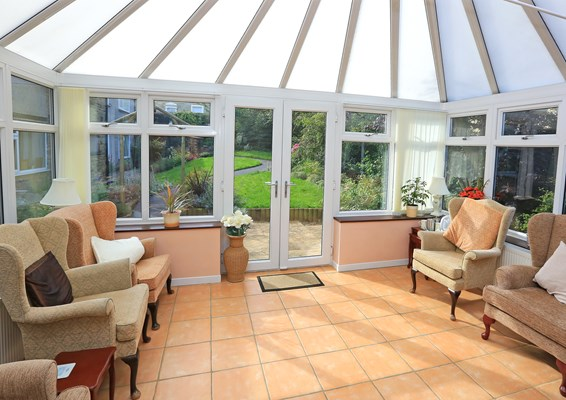 Bright conservatory with ample seating and views of the garden