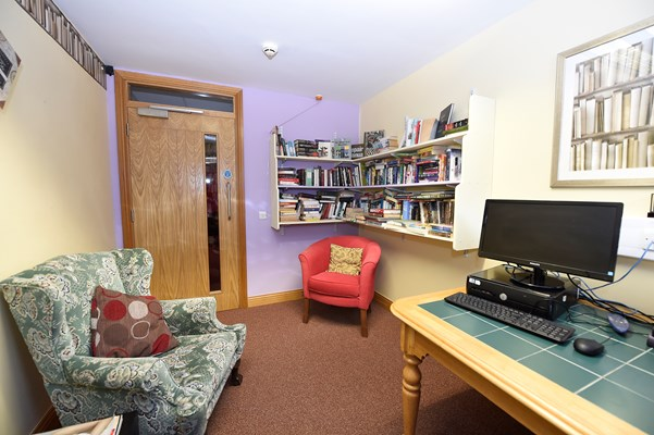 A room with a computer, bookshelves and seating