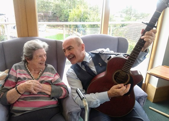 A man with with a guitar playing for a resident