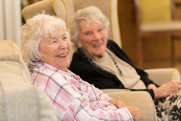 Two ladies sat laughing together