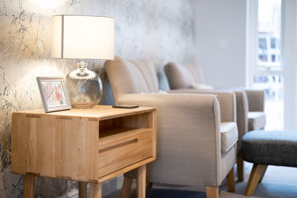 A side table with a lamp next to two armchairs
