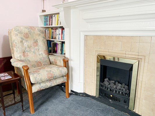 Armchair next to a reading bookcase and fireplace where residents can stay cosy whilst reading a book
