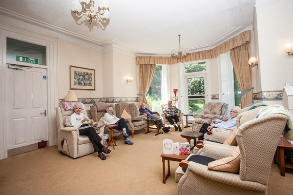 The bright spacious lounge with residents sat together