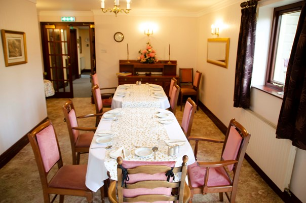 Dining area with long table and pink chairs