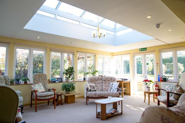 Bright and airy conservatory with ample seating and skylight at Abbeyfield House