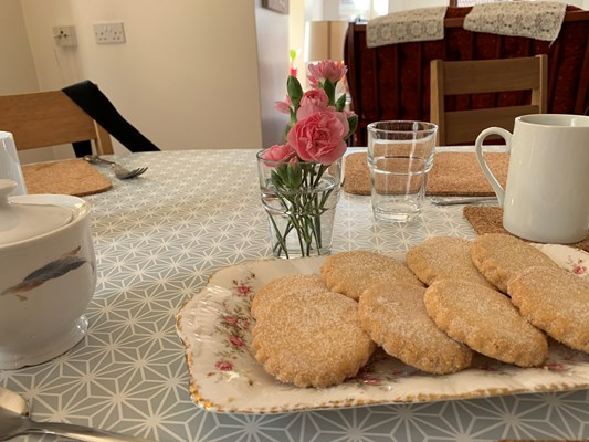 A close up of a plate of shortbread biscuits and flowers on a table