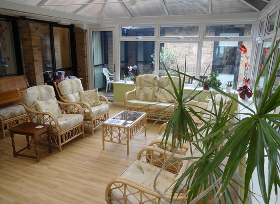 Bright and spacious conservatory with seating where residents can relax and enjoy the view of the garden